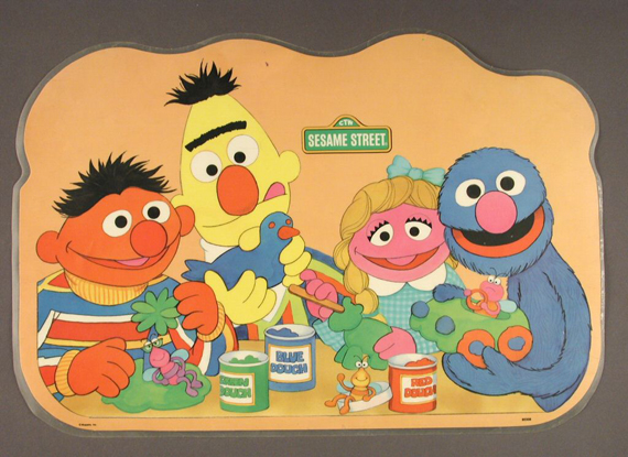 Ernie, Bert, Prairie Dawn, and Grover bond over Play-Doh. Sesame Street place mat, about 1992, gift of William J. Tribelhorn, courtesy of The Strong, Rochester, New York.