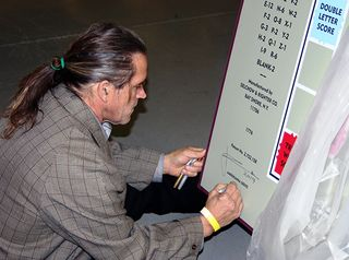 Photograph of John Kahn signing and numbering Scrabble game sculpture, December 2, 2014. Photograph courtesy of The Strong, Rochester, New York.